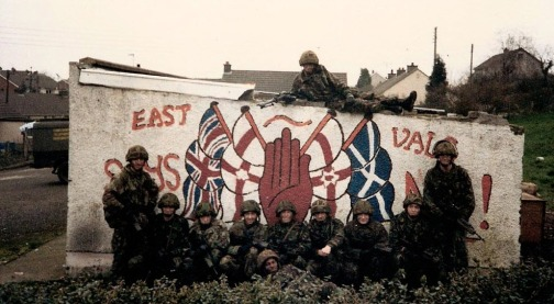 British troops pose in front of a wall decorated with British terrorist symbols during the conflict in the British Occupied North of Ireland