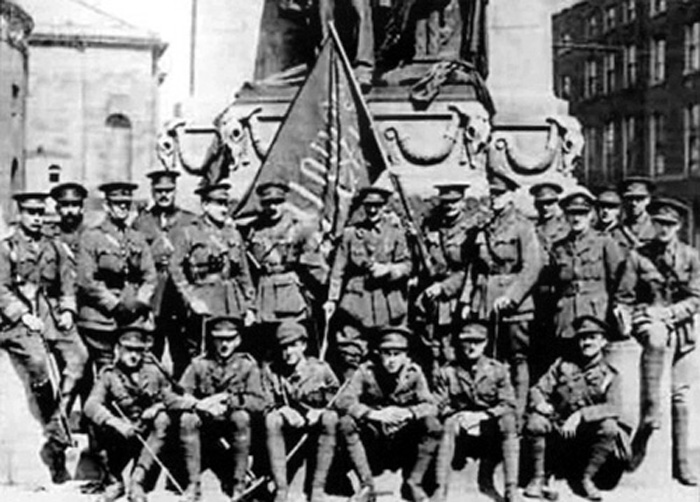 A group of British army officers pose beneath the statue of Parnell with the 'Irish Republic' flag that had flown over the GPO in O'Connell Street during the Easter Rising in 1916