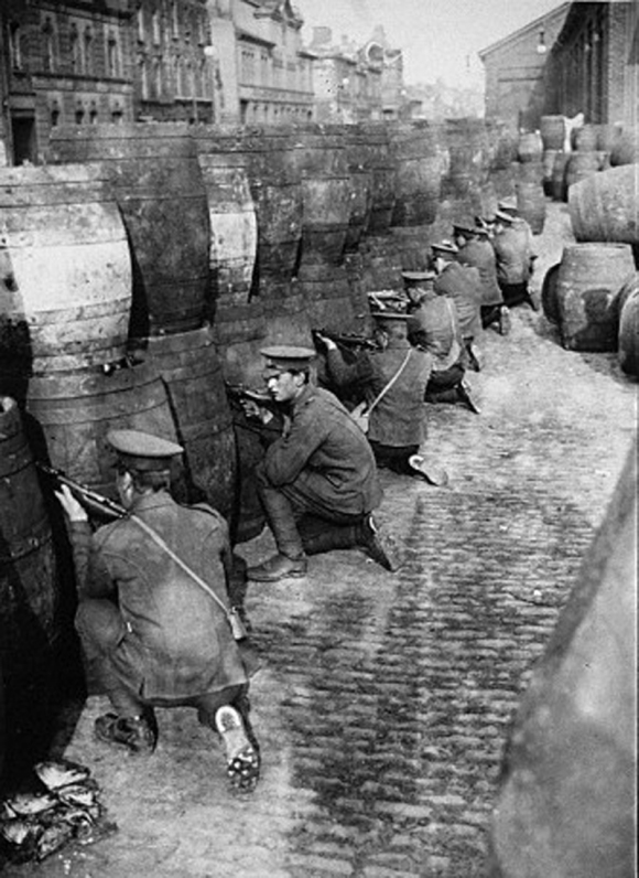 Members of the British Occupation Forces in Dublin shelter behind an improvised barrier made up of wooden barrels during or shortly after the Easter Rising of 1916