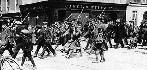 POWs of the Irish Republican Army under British military escort being marched through the city-centre of Dublin in the aftermath of the Easter Rising of 1916