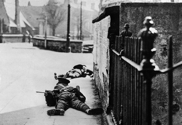 During fighting in the southern outskirts of the city-centre British troops crawl over a bridge while under fire, with possibly the body of a dead soldier in the background. The Easter Rising of 1916