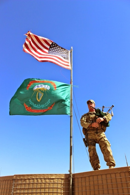 A soldier from the 69th Infantry Regiment of the New York Army National Guard stands with Irish warpipes and a Fenian-style banner, Afghanistan