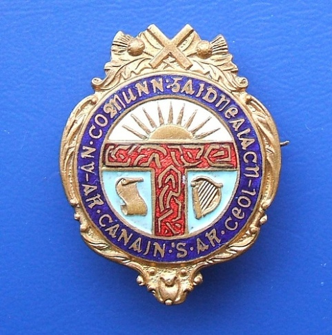 An early badge of the Scottish-speaking (Gaelic) rights movement An Comunn Gaidhealach with the Fenian Sunburst symbol as a sun rising above the horizon, Scotland