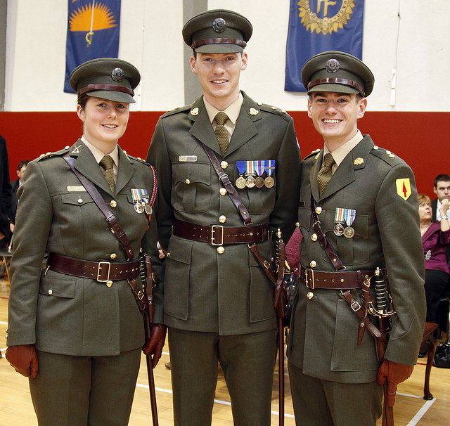 Picture of newly commissioned officers, Óglaigh na hÉireann (Irish Defence Forces) with An Gal Gréine, the Sunburst banner in the background, 2011