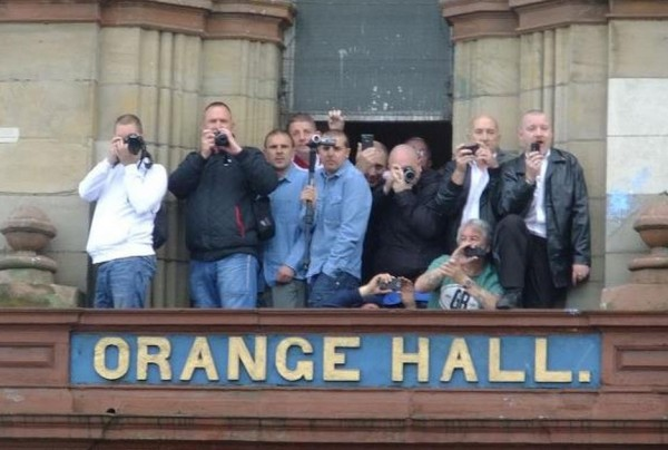Alleged British Unionist militants record the faces of people taking part in an Irish Republican parade from an Orange Order building, Belfast, British Occupied North of Ireland, 2012, contradicting yet again the Orange Order's repeated denials of links to organised violence (Photo: The Newlodge Facebook Page)