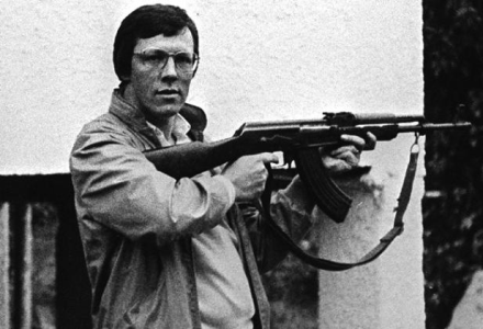 Peter Robinson with an automatic assault rifle