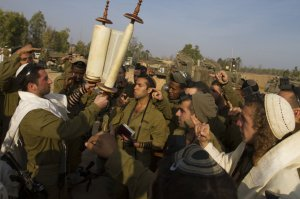 Israeli soldiers pray before a Torah, southern Israel, 2012 (AP Photo - Ariel Schalit)