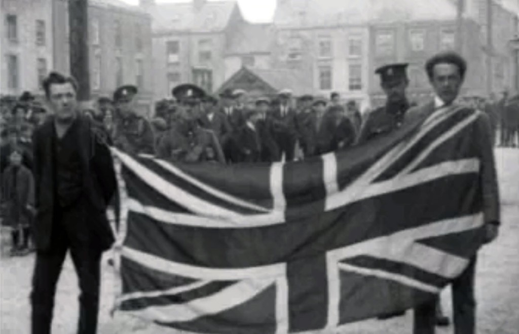 Two Irishmen forced to parade around by British troops with a British flag tied around their necks