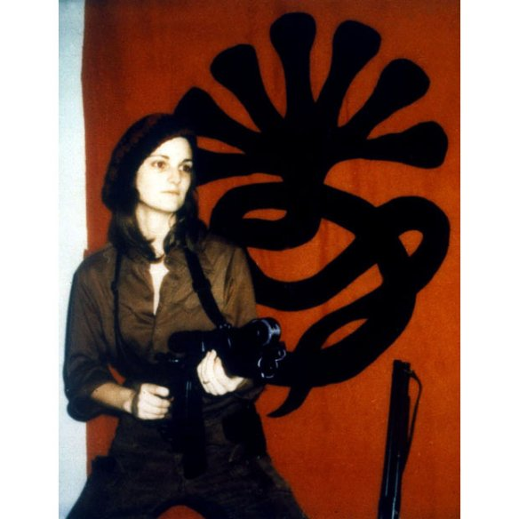 Patty Hearst in front of the insignia of the Symbionese Liberation Army (SLA)