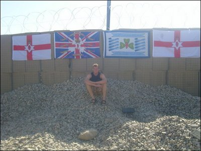 A British soldier in Afghanistan poses in front of several British terrorist and extremist flags celebrating the conflict in the north-east of Ireland