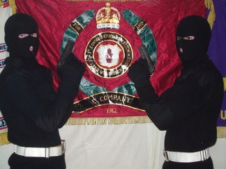 In Ireland gunmen of the UVF, a British terrorist organisation, pose in front of an extremist flag