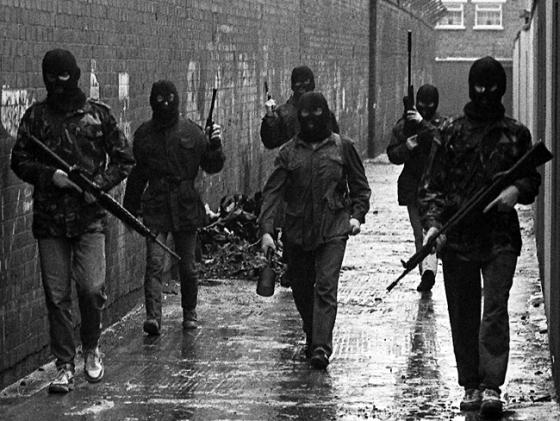 """An Active Service Unit of the Irish Republican Army moves through Belfast, the Volunteer in the middle holding an anti-armour """"drogue grenade"""", British Occupied North of Ireland, c.1980s"""