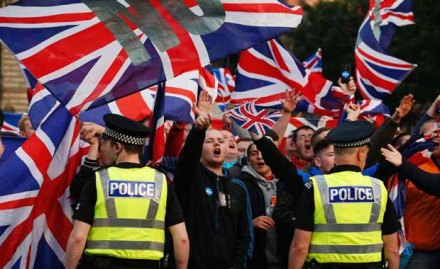 Extreme British unionist and nationalist supporters holding Union Jacks and giving Nazi salutes in Glasgow, Scotland