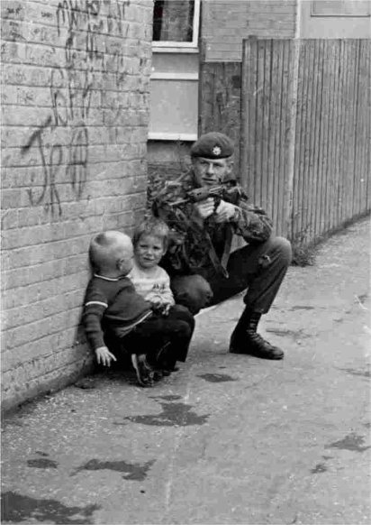 A British soldier on foot patrol in Belfast, Ireland, using two young Irish boys for cover