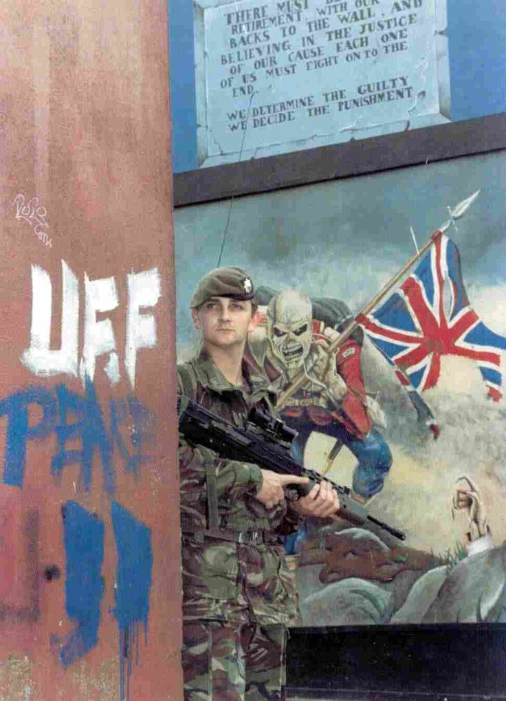 A British soldier standing in front of British terrorist wall-murals and slogans, Belfast, Ireland