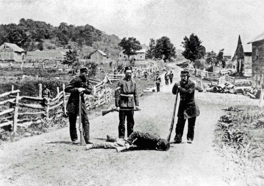 British militiamen stand over the body of a slain soldier of the Irish Republican Army following the Battle of Eccles Hill, the Second Fenian Invasion of Canada 1870