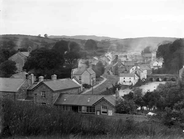 The main street of Pettigo, with the bridge into the village on the top right, and the train station to the fore, c.1900