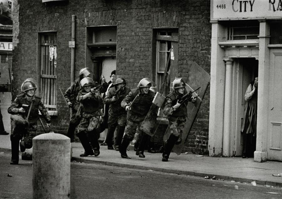 British Army soldiers attack demonstrators while Irish civilians cower in their doorways, UK Occupied North of Ireland