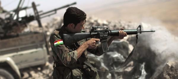 An Iraqi Kurdish Peshmerga fighter fires on Islamic State insurgents