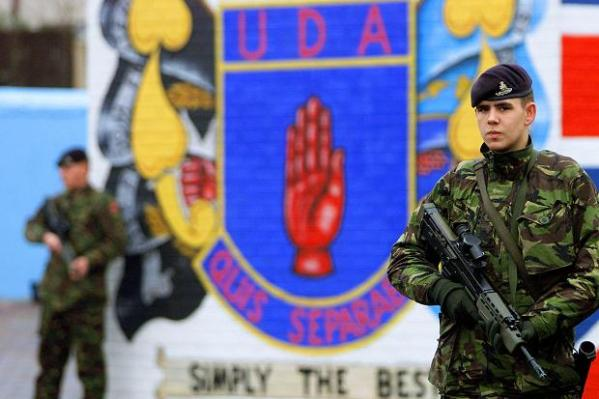 British soldiers stand beside a wall mural marking the territory of the UDA, a then legal UK terrorist faction in Ireland