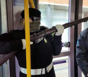 A volunteer of the Irish National Liberation Army or INLA displays an imitation or deactivated rifle on public transport in Dublin, 2016